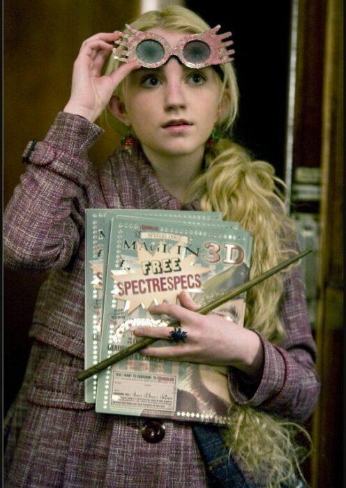 luna lovegood sujetando un libro, su varita y unos lentes en Harry Pottter