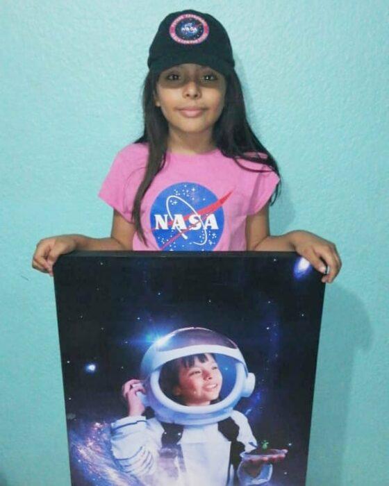 Adhara Pérez mostrando un cuadro donde ella es astronauta