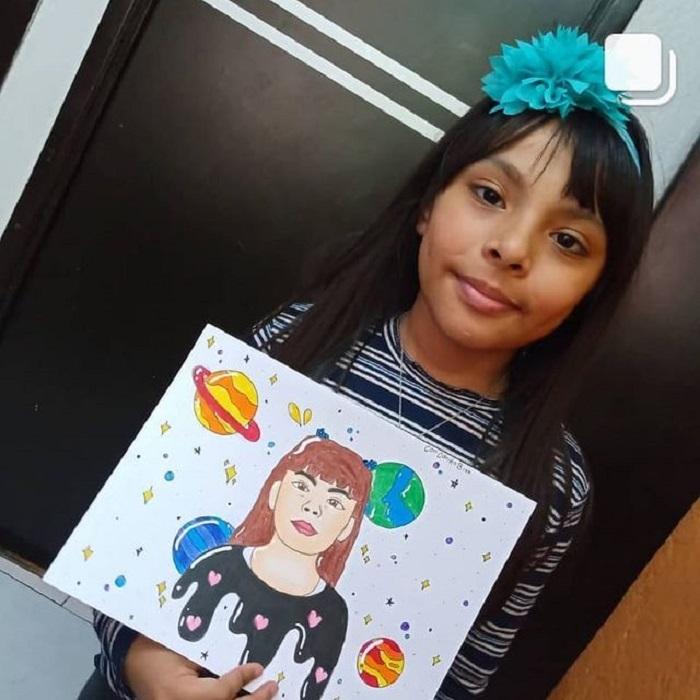 Adhara Pérez mostrando un dibujo de ella y los planetas