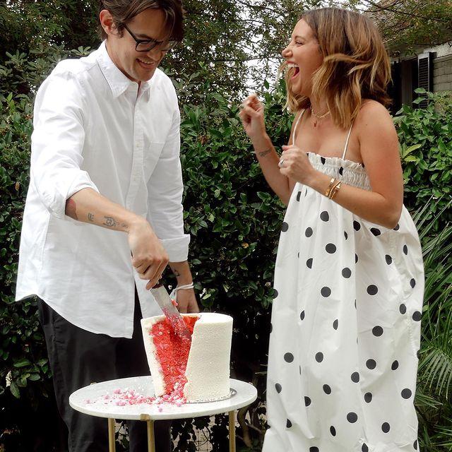 Ashley Tisdale y su esposo cortando un pastel para la revelación de sexo de su bebé