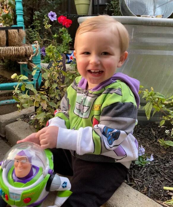 Niño sonriendo al tener de vuelta a su muñeco Buzz Lightyear; Buzz Lightyear regresa con su pequeño amigo fiel después de extraviarse en un avión
