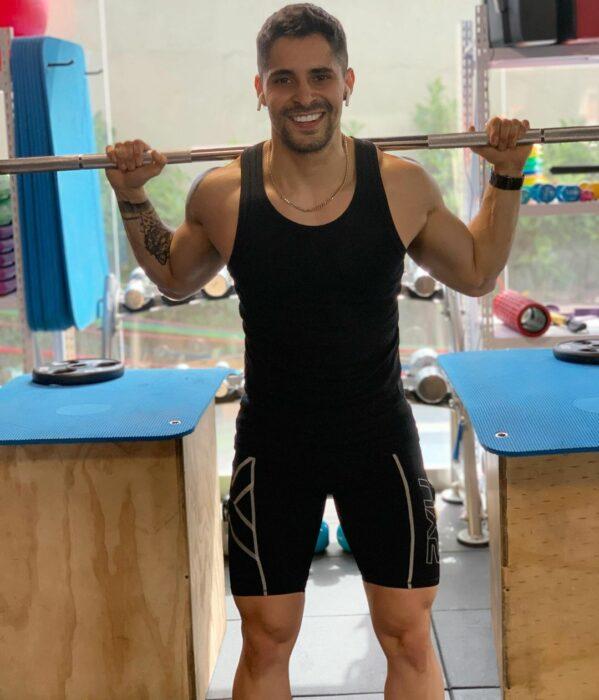 Chico haciendo ejercicio con una barra de pesas en el gimnasio