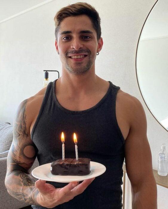 Chico festejando su cumpleaños y sosteniendo un pequeño pastel con una velita
