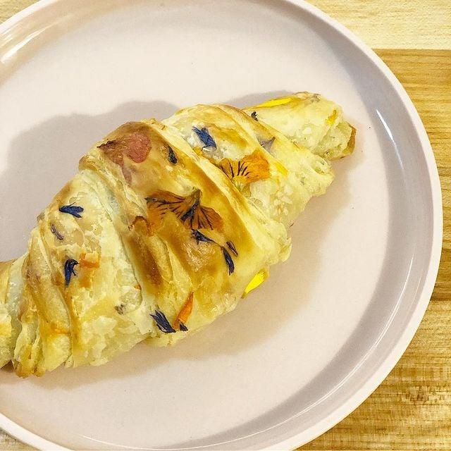 Croissant de mantequilla decorado con flores de colores; Crea deliciosa repostería con flores