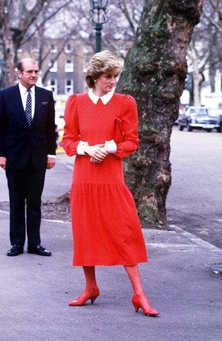 Diana de gales usando un vestido de color rojo con medias del mismo color y zapatos