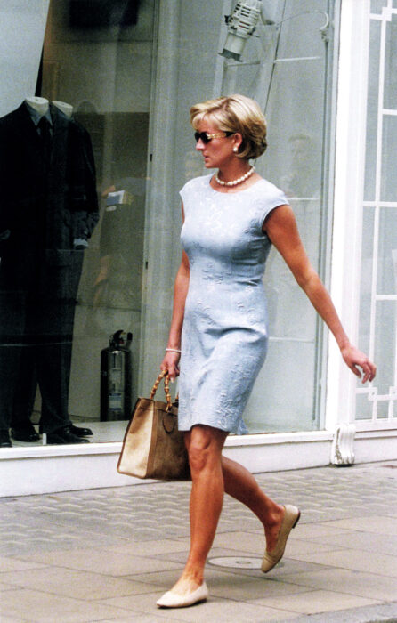 Lady Di caminando por la calle mientras sostiene su bolso y usa un vestido de color azul con flats
