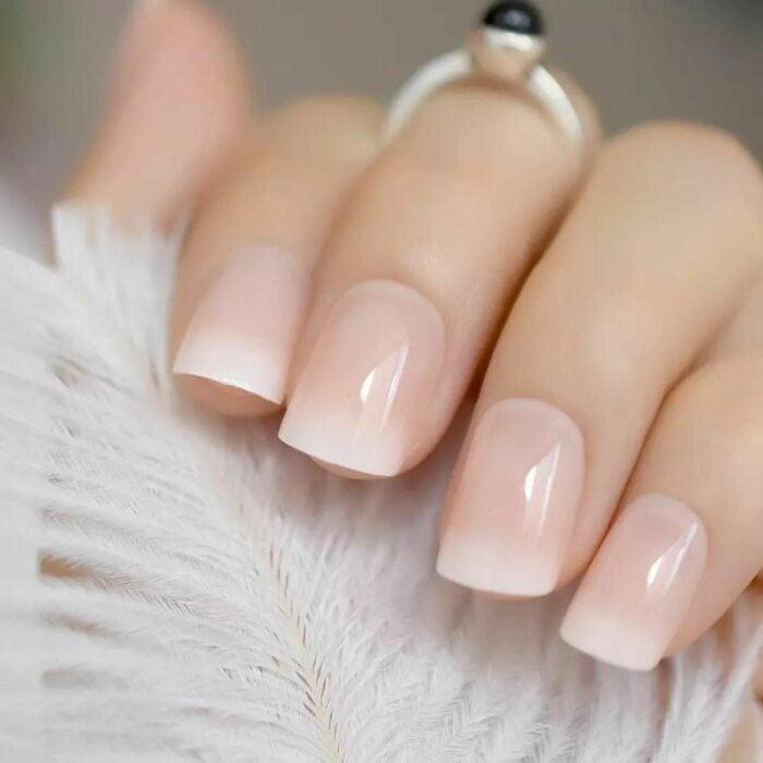 Chica mostrando sus uñas con un diseño ombré french