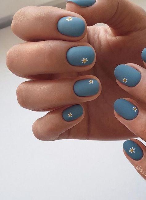 Diseño de uñas en color azul tierra con decorado floral