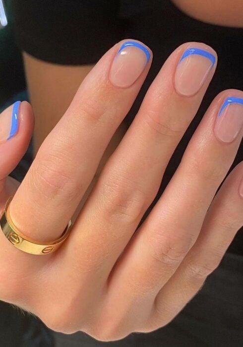 Diseño de uñas en tono nude con un color en azul en la punta