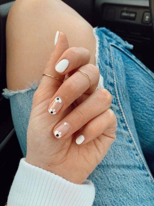 Diseño de uñas en tono blanco con pequeñas flores de color negro