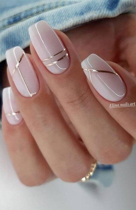 Diseño de uñas en color rosa con detalles metálicos dorados