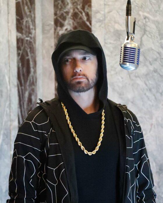 Eminem usando una playera negra, sudadera con detalles grises y una cadena dorada