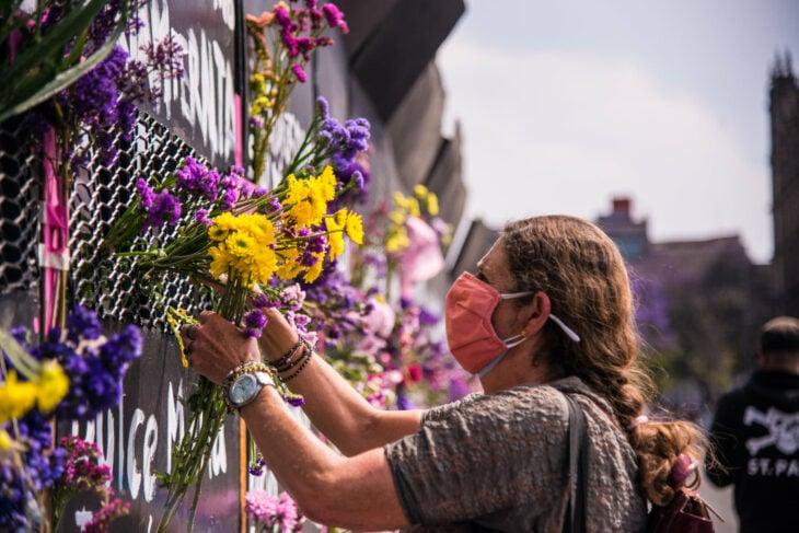 Mujer colocando flores sobre una vaya colocada para frenar las marchas del 8 de marzo 2021
