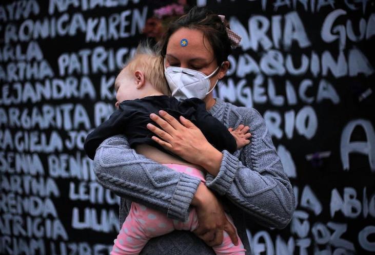 Mujer sosteniendo a su bebé en brazos mientra sestá en la marcha de 8 marzo 2021