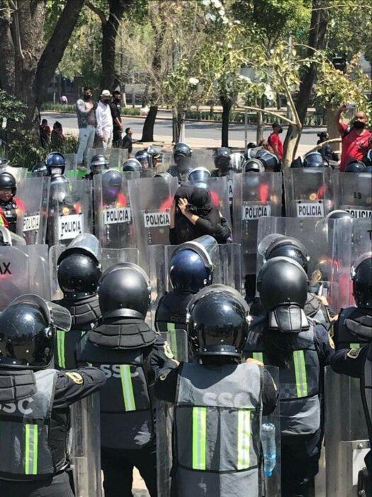 Mujeres abrazadas mientras están rodeadas de policías el 8 de marzo de 2021