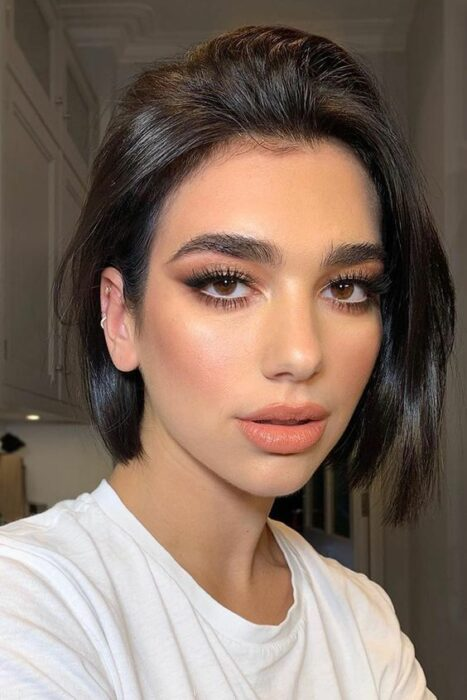Dua Lipa with bob cut in glossy black tone