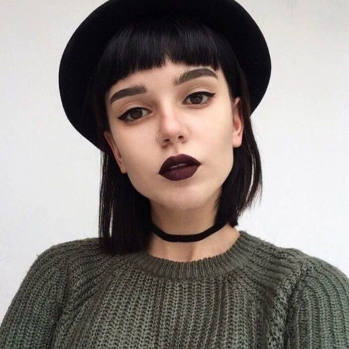 Girl with short hair and fringes in glossy black tone, and black hat