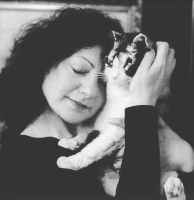 Chica sosteniendo a un gatito en brazos y dándole un beso