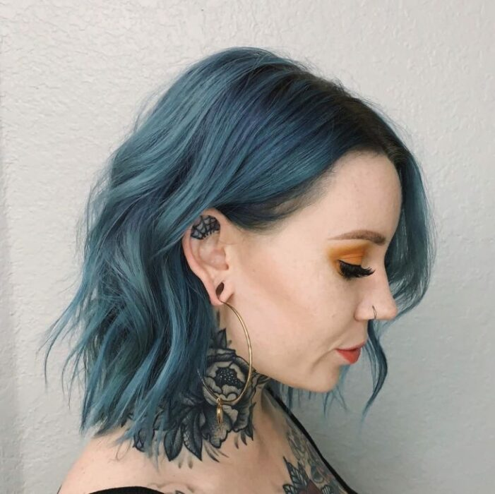 Girl with short hair dyed in blue tone with greenish highlights