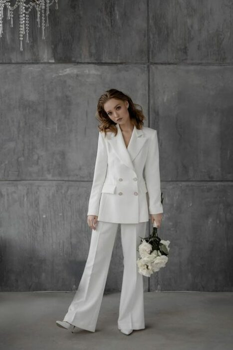 Girl wearing a white suit while holding a white blazer