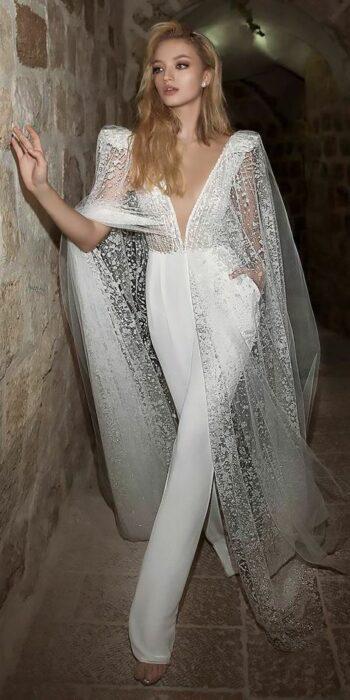 Chica usando un jumpsuit de color blanco con una capa en los hombros llenos de brillo