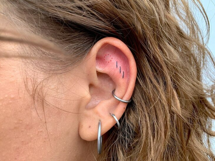 Girl with a tattoo on her ear in the form of colored dots