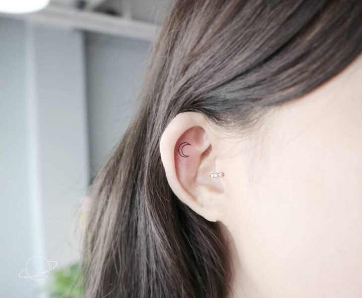 Girl with a moon-shaped ear tattoo