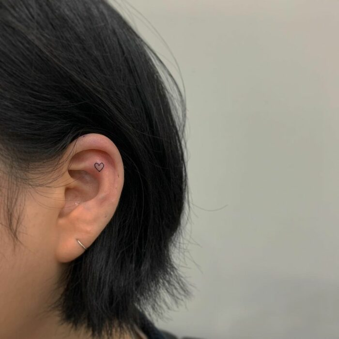 Girl with a tattoo on her ear in the shape of a heart