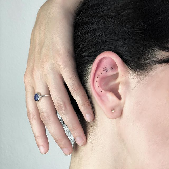 Girl with a tattoo on her ear in the form of dots that form a flower