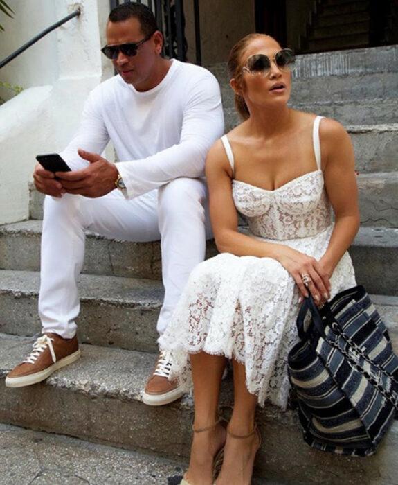 Jennifer Lopez y Alex rodriguez sentados en unas escaleras mirando sus teléfonos