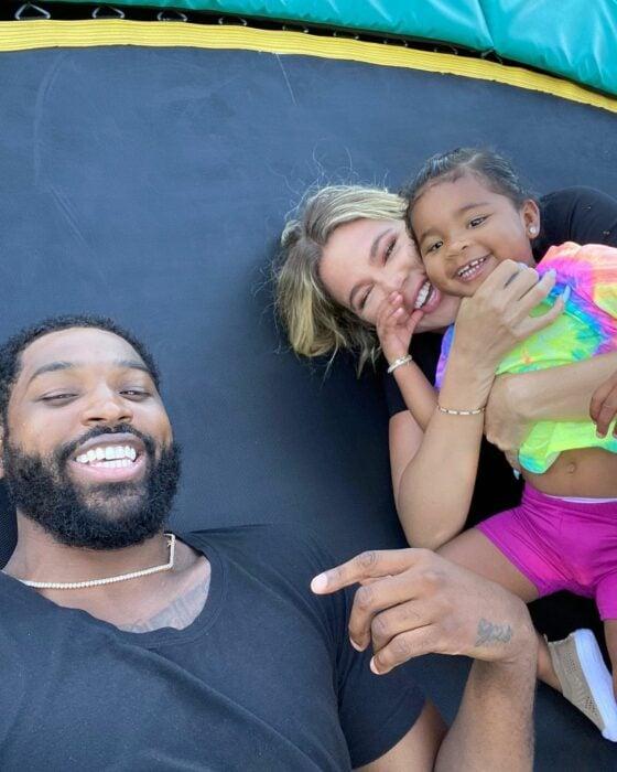 Khloe Kardashian y Tristan Thompson recostados en una cama elastica jugando con su hija True