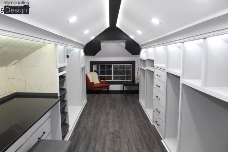 Armario en el ático terminado con gabinetes, sillones y pintura de color blanco
