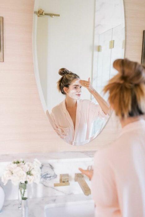 Chica frente al espejo aplicándose una mascarilla; Mascarillas con huevo para una piel bonita