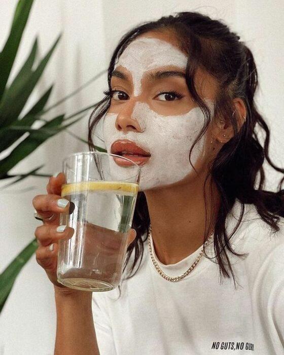 Chica llevando mascarilla y bebiendo agua; Mascarillas con huevo para una piel bonita