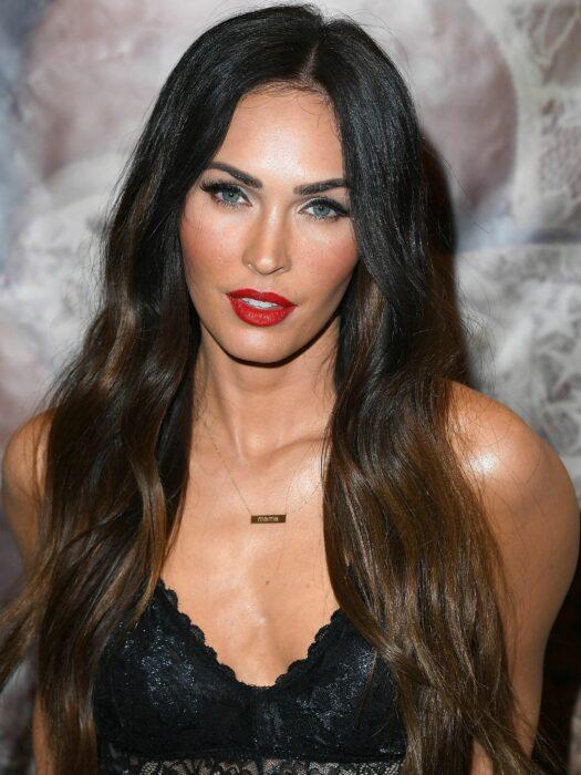 Megan Fox con blusa negra de escote V y usando labial rojo