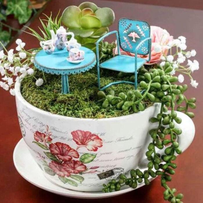 Mi jardín en taza de color blanco con diseño de rosas y varias suculentas, además de una mesa y silla de jardín color azul
