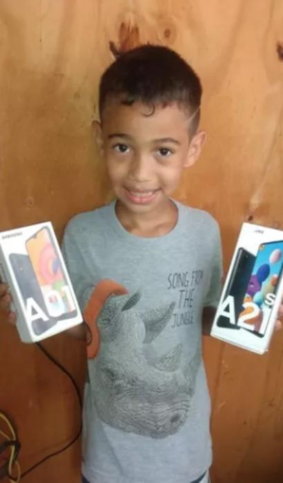 Niño sujetando en sus manos dos celulares que le regalaron en redes sociales