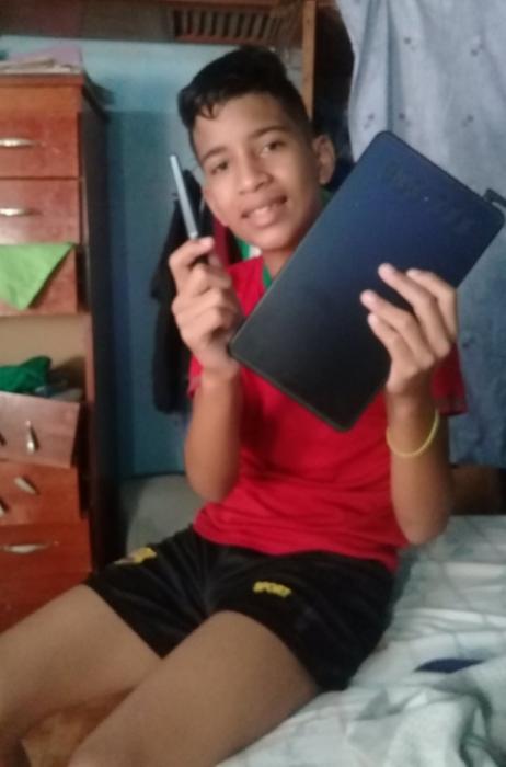 Niño Samuel Mendoza posando para una fotografía mientras sostiene una tableta