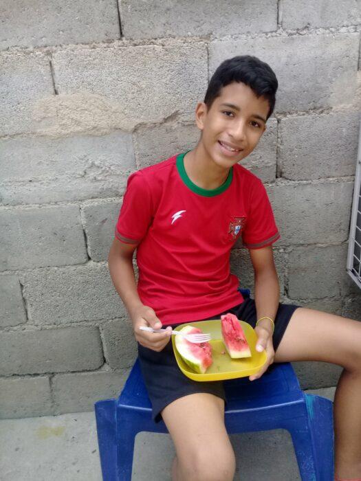 Niño Samuel Mendoza sentado comiendo fruta mientras posa para una fotografía