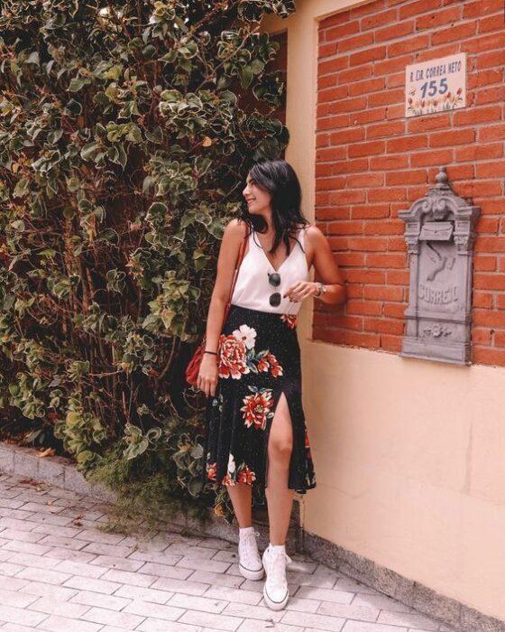 Chica usando una blusa blanca de tirantes, con falda negra de estampado de rosas y tenis blancos