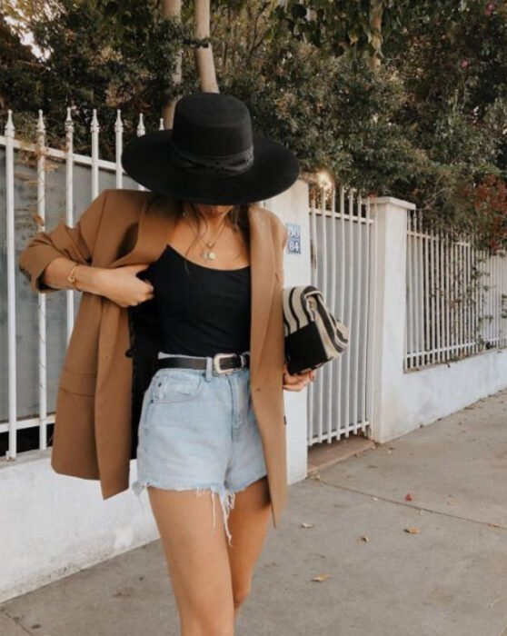 Girl wearing black tank top, light denim shorts, belt, camel blazer and black hat