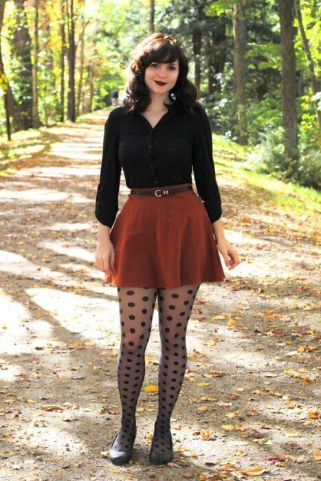 Chica usando blusa negra, falda color naranja quemado, con medias y zapatos del mismo color