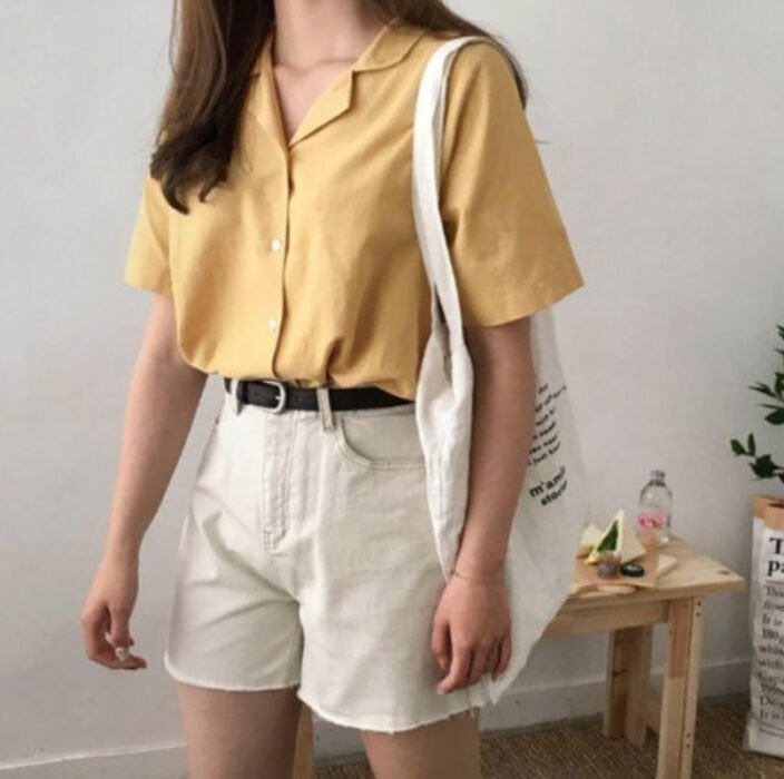 Girl wearing yellow shirt, with beige shorts and black belt