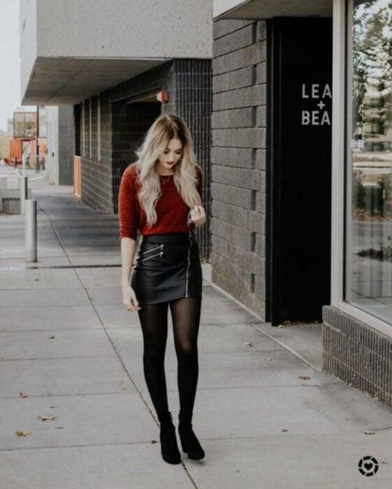 Chica usando blusa color guinda, con falda de vini piel, medias y zapatos color negro