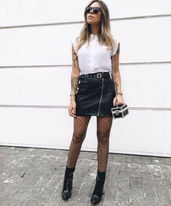 Chica usando blusa blanca, con falda, medias y botines color negro