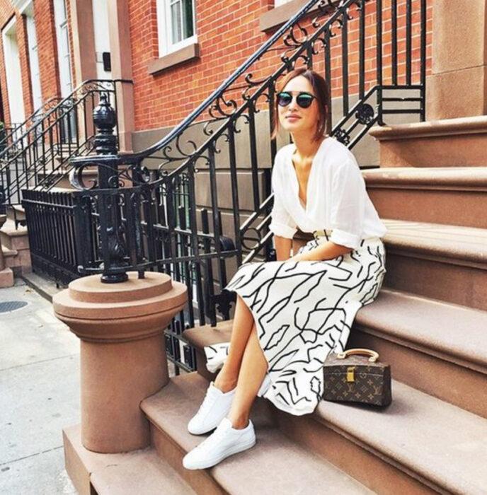 Chica usando camisa color blanco, falda del mismo color con detalles en color negro y tenis blancos