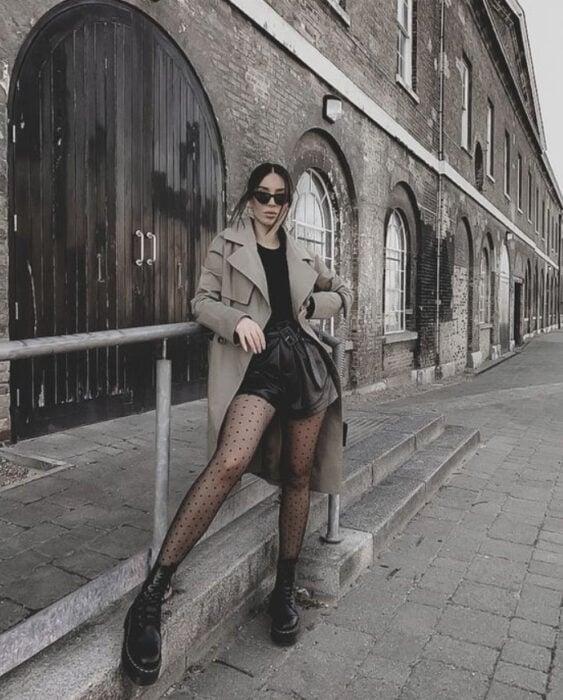 Chica usando gabardina color arena, short y blusa negra, con medias y botines del mismo color