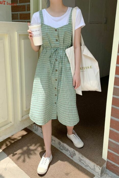 Girl wearing a long green sundress with white squares, a white long-sleeved shirt underneath and white tennis shoes