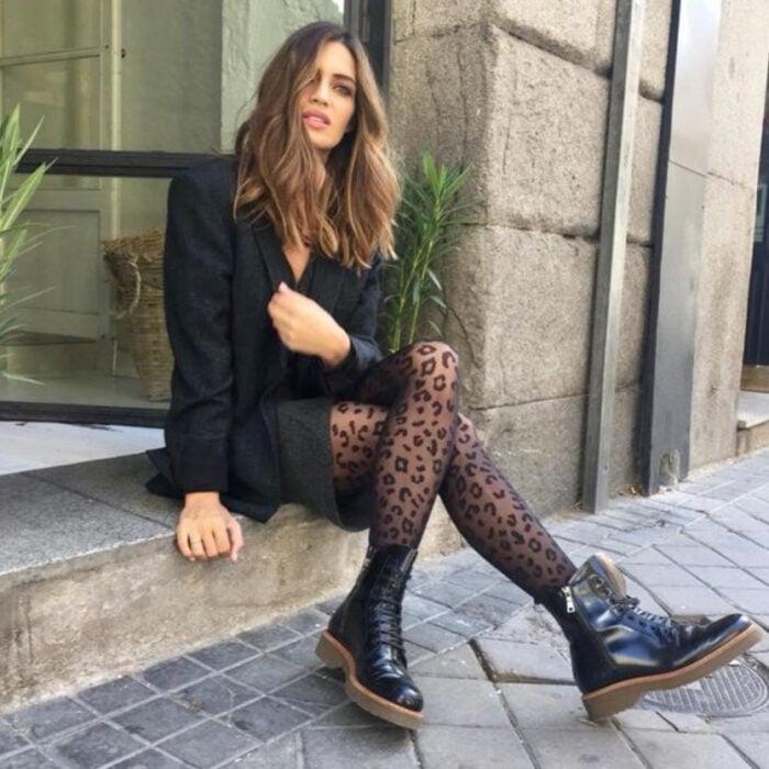 Chica usando falda, blusa, blazer, medias y botines color negro
