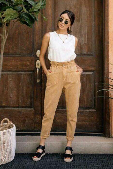 Chica usando una blusa blanca de cuello redondo sin mangas y pantalón color caki, con sandalias color negro